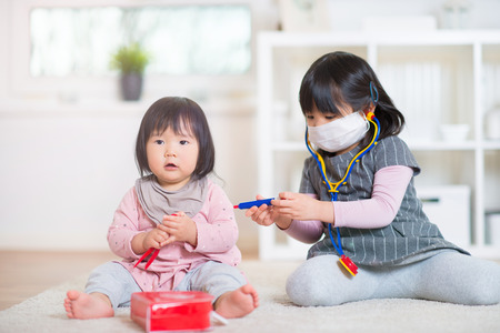 Two happy japanese sisters playing with medical set on white capet at home