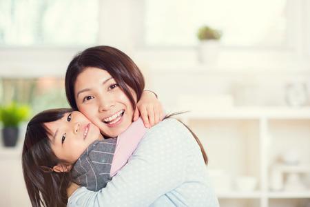 Portrait der glücklichen japanischen Mutter umarmt mit ihrem süßen kleinen Tochter zu Hause Standard-Bild - 71641962
