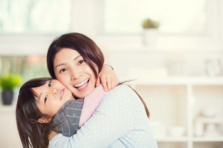 Portrait of happy japanese mother hugging with her cute little daughter at home Фото со стока - 71641962