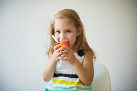 niños desayunando: Adorable niña niño comiendo un yogur de frutas en el hogar Foto de archivo