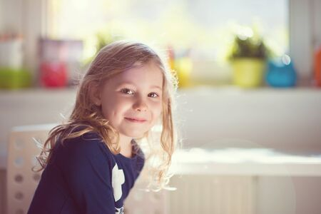 interrior: Excited face of pretty small girl at sunny day at home Stock Photo