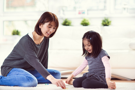 Pretty happy japanese mother play with her cute little daughter at home