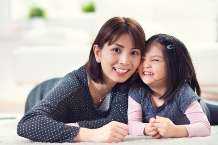 Pretty happy japanese mother play with her cute little daughter at home Фото со стока - 71429631