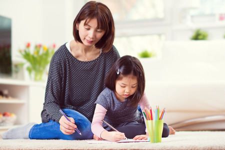 asian tulips: Pretty happy japanese mother play and draw with her cute little daughter at home