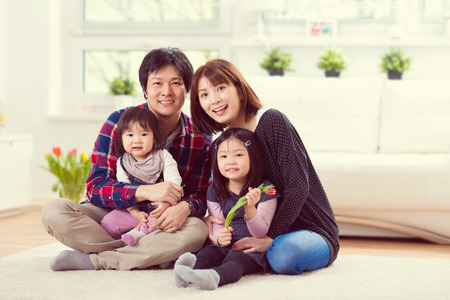 Young happy family with toddler pretty daughters playing together and having fun at home