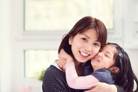 mujer enamorada: Retrato de la madre japonesa feliz abrazando a su pequeña hija linda en el hogar