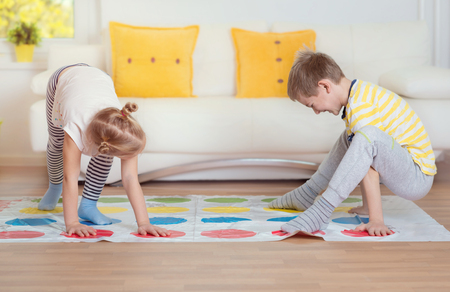 Two happy children playing exciting game at light home