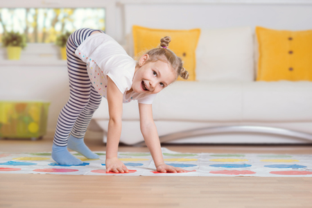 exciting: Pretty little girl have fun playing exciting game at home