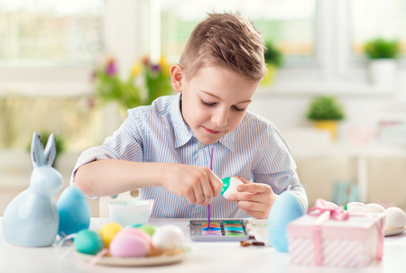 Happy child boy having fun during painting eggs for Easter in spring at home photo