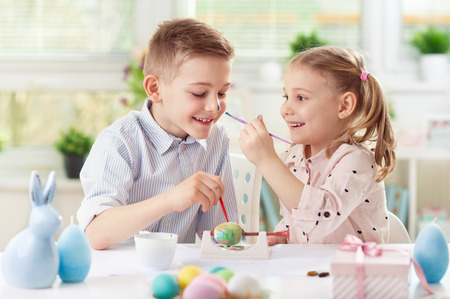 Two happy children having fun during painting eggs for Easter in spring time photo