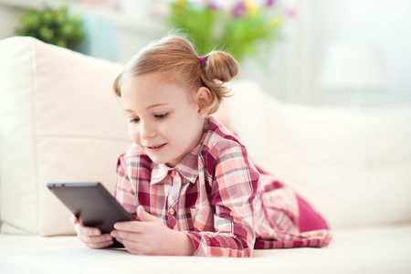 Pretty little child girl  using a digital tablet, looking and smiling while lying on the whitw couch at home