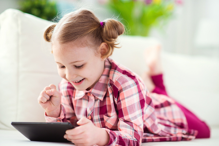 whitw: Pretty little child girl  using a digital tablet, looking and smiling while lying on the whitw couch at home