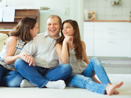 Portrait of young happy family with pretty teenager daughter having fun together at home