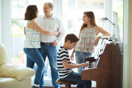 lifestile: Happy young family listening how cildren plays piano music at home