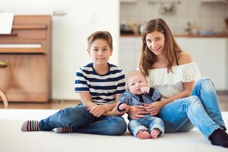 Portret van jonge mooie tiener met haar baby broer en 9 jaar oude broer