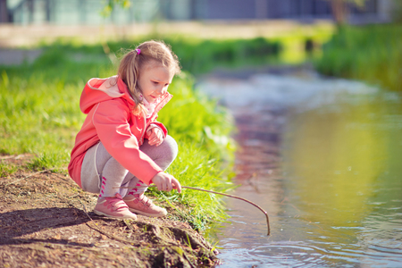 Happy adorable little blonde girl playing near pond in sunny day