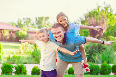 Portrait of happy father and two cute children playing at home  courtyard photo