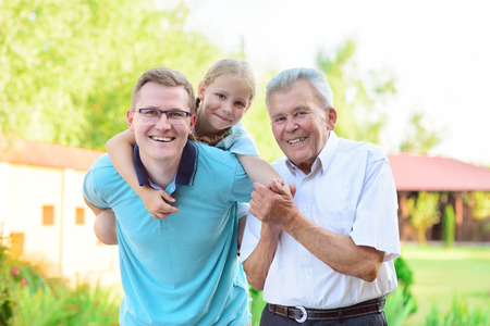 Portrait of happy old grandfather and cute children in summer photo