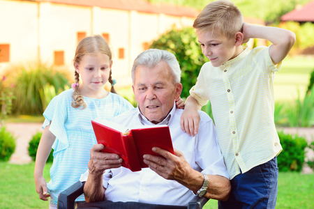 Happy old grandfather reading book for his cute grandchildren  in garden photo