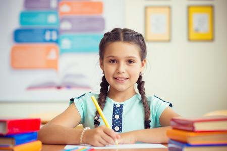 Cute smiling schoolgirl at school during lesson