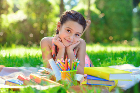 Portrait of pretty young girl reading book at sunny day in park