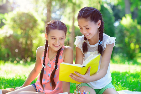 Happy hispanic girls drawing and studying in summer park Stockfoto