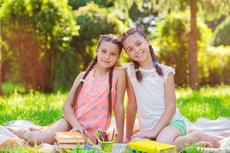 Zwei hübsche kleine Mädchen lesen am Sunnt Tag im Park Standard-Bild - 85264542