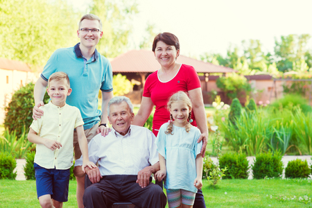 Portrait of big happy family with old grandfather, his daughter and his grandchildren in garden Stock Photo