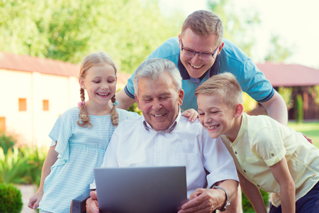 grandaughter: Happy family with grandfather having fun during internet talking on laptop Stock Photo