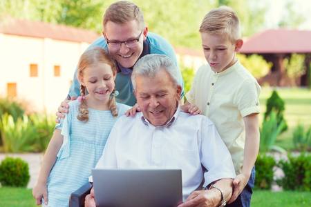 Happy family with grandfather having fun during internet talking on laptop Stock Photo