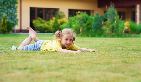 Portrait of little happy girl playing barefoot badminton at garden near her modern house Stock Photo