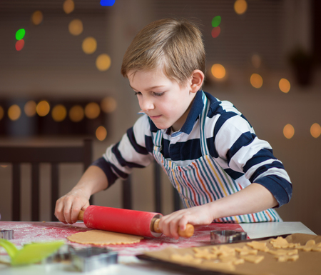 Happy little child preparing cookies for Christmas and New Year at home Standard-Bild