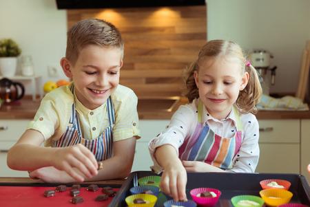 Twee gelukkige kinderen die Kerstmiskoekjes en muffins bakken bij moderne keuken