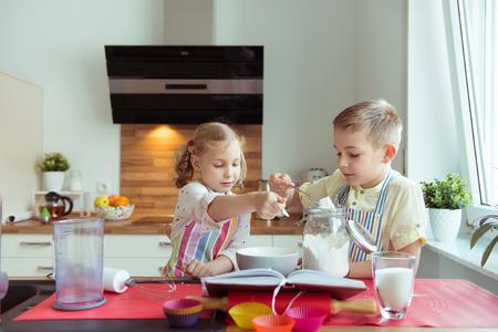 Twee gelukkige kleine en leuke kinderen die muffins voorbereiden thuis bij moderne keuken