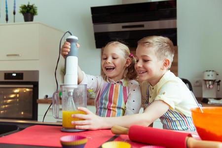 Portret van twee gelukkige en schattige kleine kinderen die plezier hebben tijdens het voorbereiden van muffins met mixer in moderne keuken Stockfoto