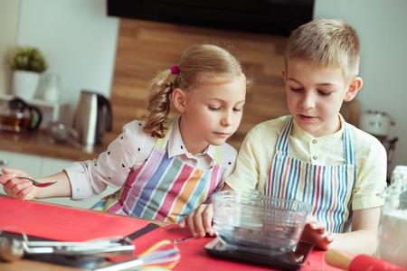 Portret van twee gelukkige kinderen die die pret hebben tijdens het koken van Kerstmiskoekjes bij moderne keuken