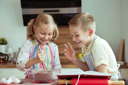 Portrait of two happy children which having fun during cooking christmas cookies at modern kitchen