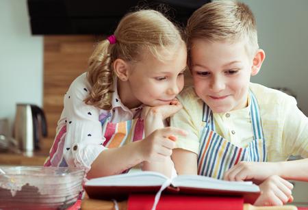 Twee mooie en gelukkige kinderen die pret hebben die recept onderzoeken alvorens Kerstmiskoekjes op te stellen Stockfoto