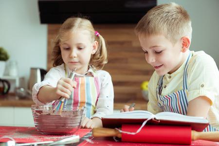 Twee gelukkige kinderen die Kerstmiskoekjes bakken bij moderne keuken
