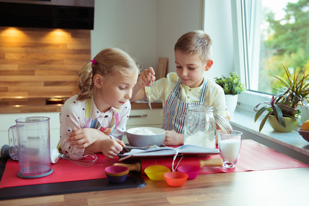Two happy little and cute children preparing muffins at modern kitchen at home Stock fotó