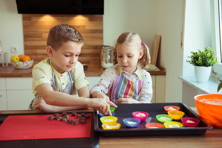 Two happy children baking christmas cookies and muffins at modern kitchen