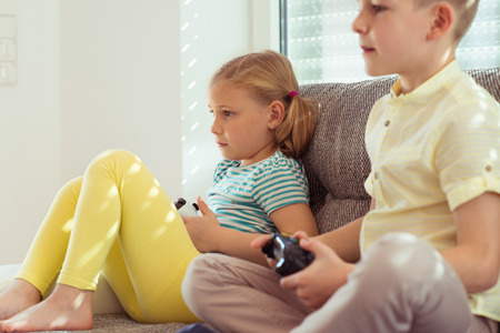 Two happy children playing video games with console at home Zdjęcie Seryjne