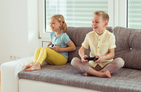Two happy children playing video games with console at home Foto de archivo