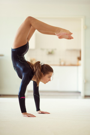 Young pretty girl has training gymnastics at home in black leotard in white interior