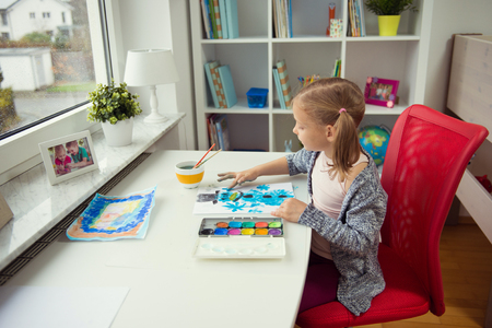 Pretty little child girl painting winter with colorful paint at home