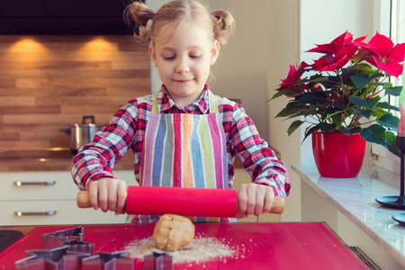 Pretty little girl with funny pigtails rolling dough for christmas cookiess in modern kitchen