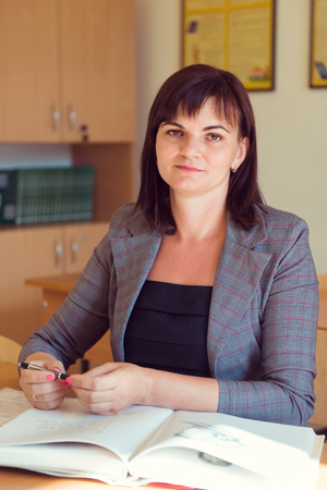 Pretty young teacher is sitting at the table with books  in classroom