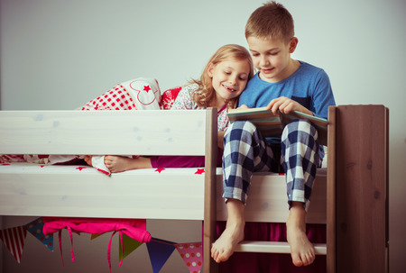Two happy sibling children reading book in bunk bed under blanket