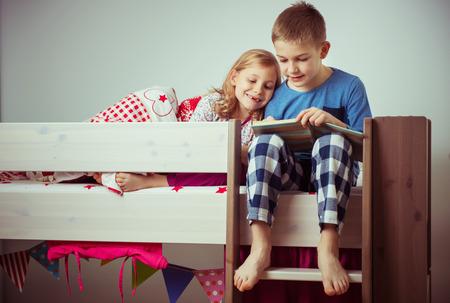 Two happy sibling children reading book in bunk bed under blanket Imagens - 93571098