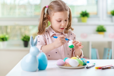 Happy pretty child girl having fun during painting eggs for easter in spring at home Stock Photo